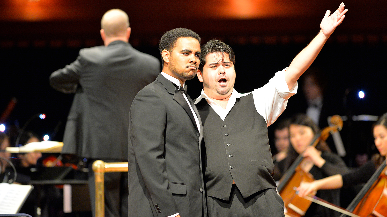Two vocalists performing in front of orchestra
